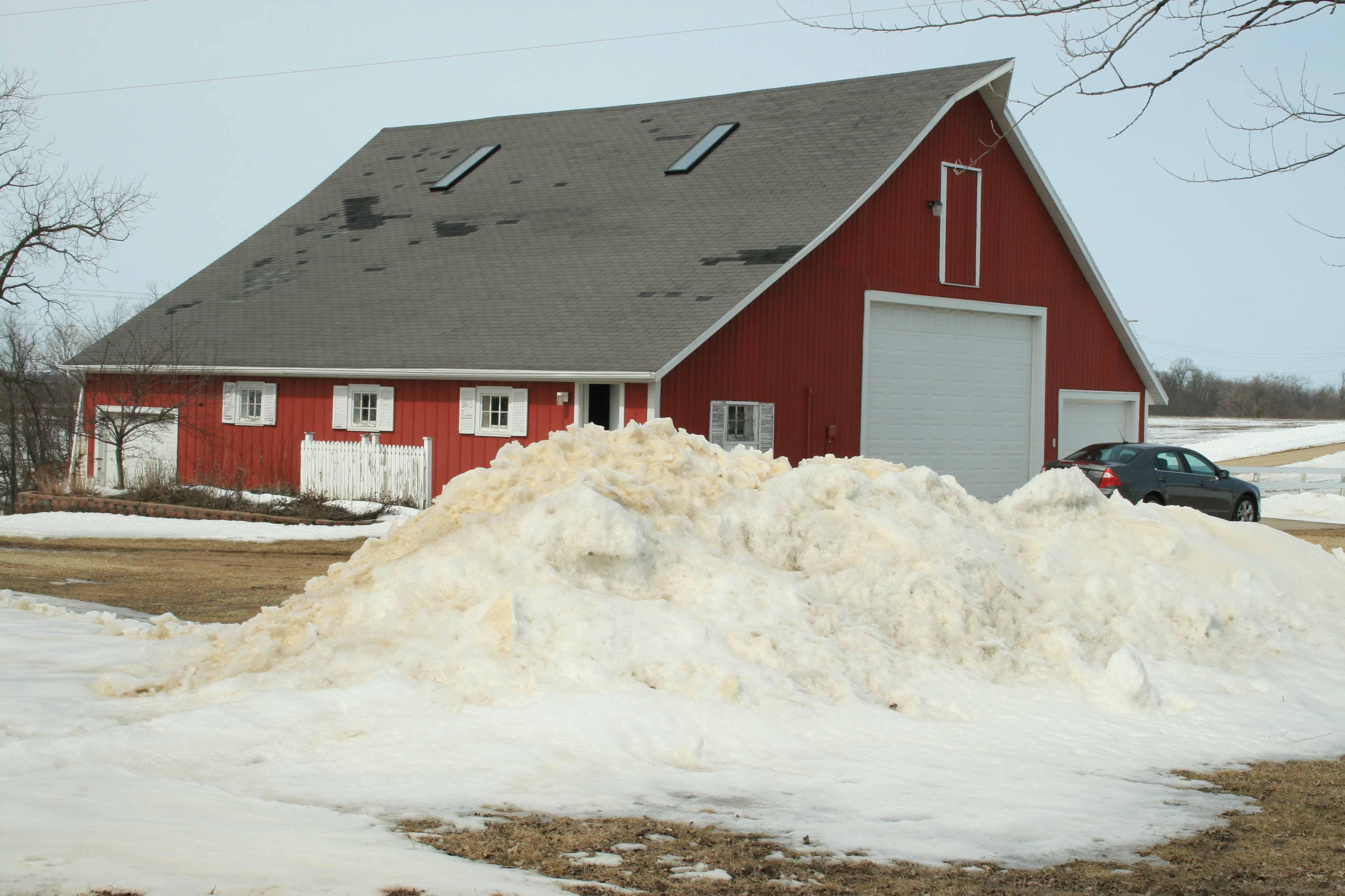 Snow plied up near the barn